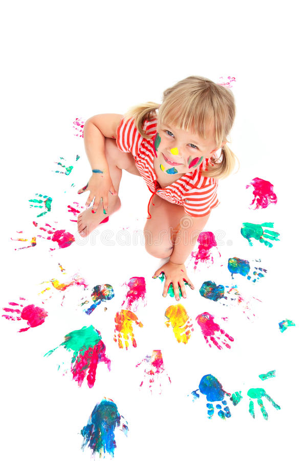 Cute little girl making colorful hand prints royalty free stock image