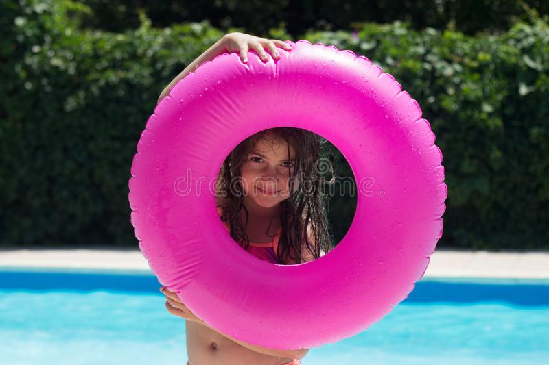 Cute little girl making fun next to pool side, playing with her swim ring, looking through it royalty free stock photos