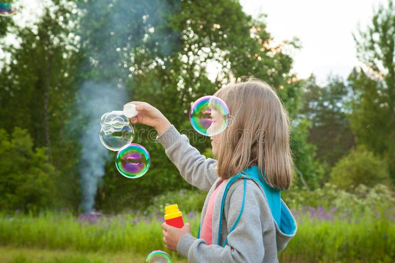 Cute little girl making soap bubbles stock images