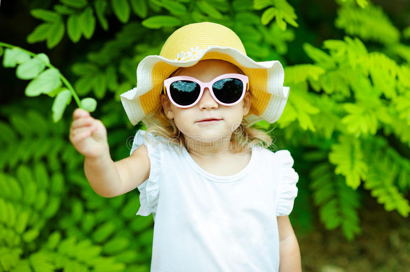Cute little girl on the meadow in spring day. Cute little girl is playing with leaves in summer park stock photos