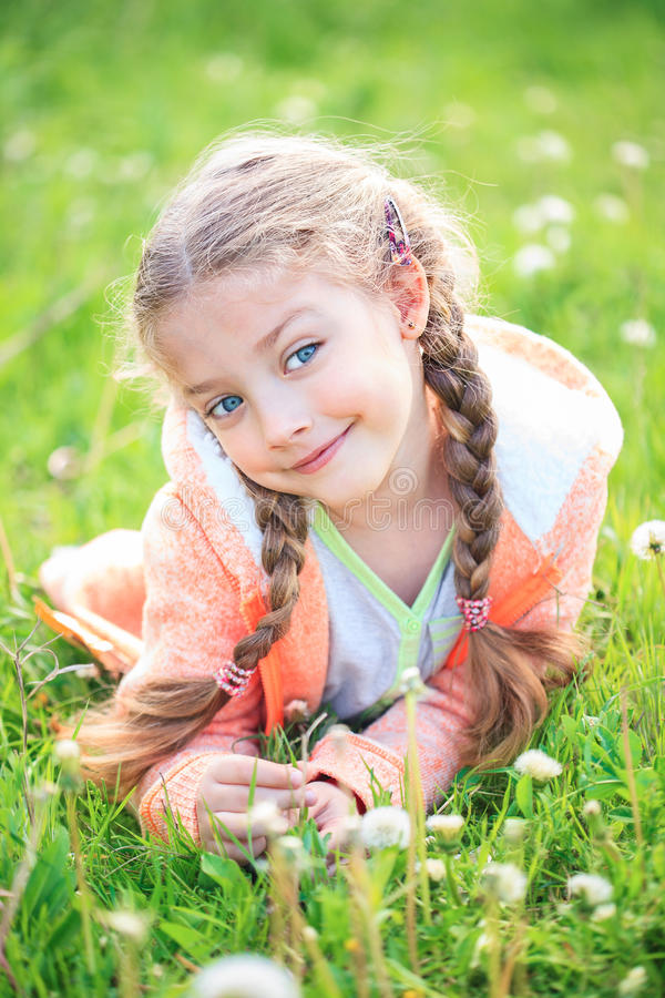 Cute little girl on the meadow in summer day royalty free stock photography