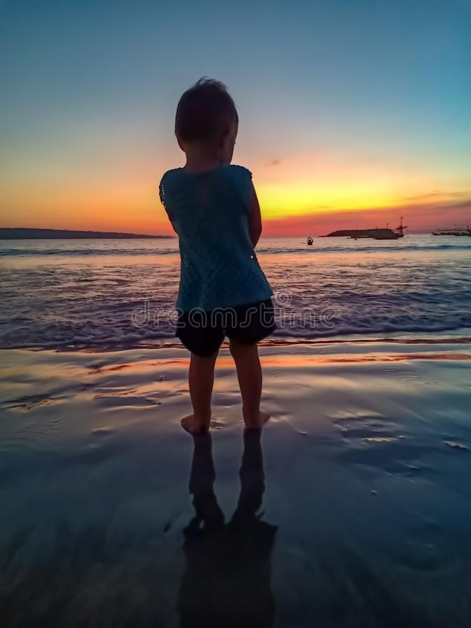 Cute little girl meet the sunset and having fun on the beach royalty free stock image