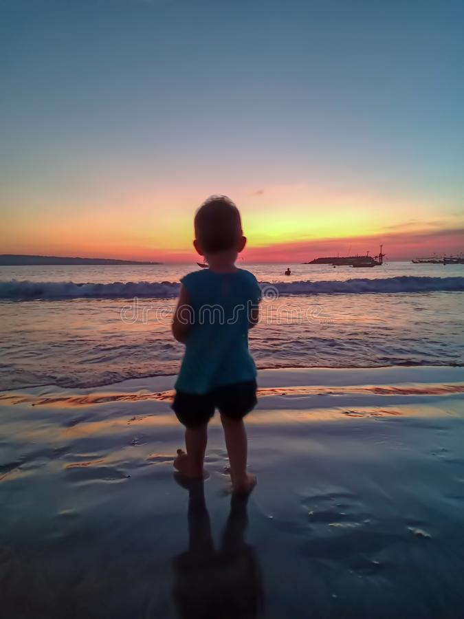 Cute little girl meet the sunset and having fun on the beach royalty free stock photos