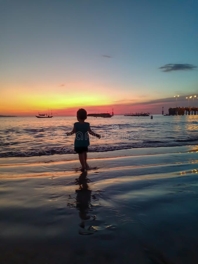 Cute little girl meet the sunset and having fun on the beach royalty free stock photo