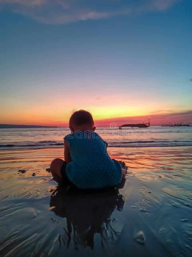 Cute little girl meet the sunset and having fun on the beach stock images