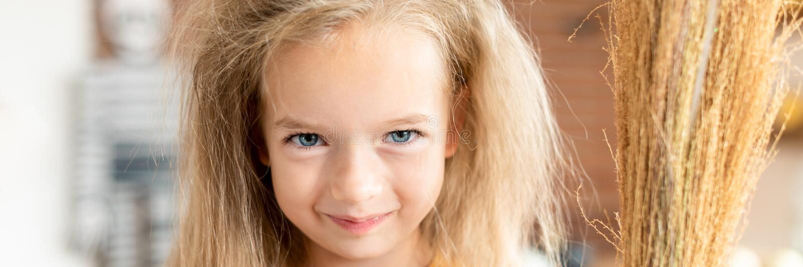 Cute little girl with messy hair, dressed up as a witch, holding a broom, looking at camera smiling. Halloween party or carnival. royalty free stock photos