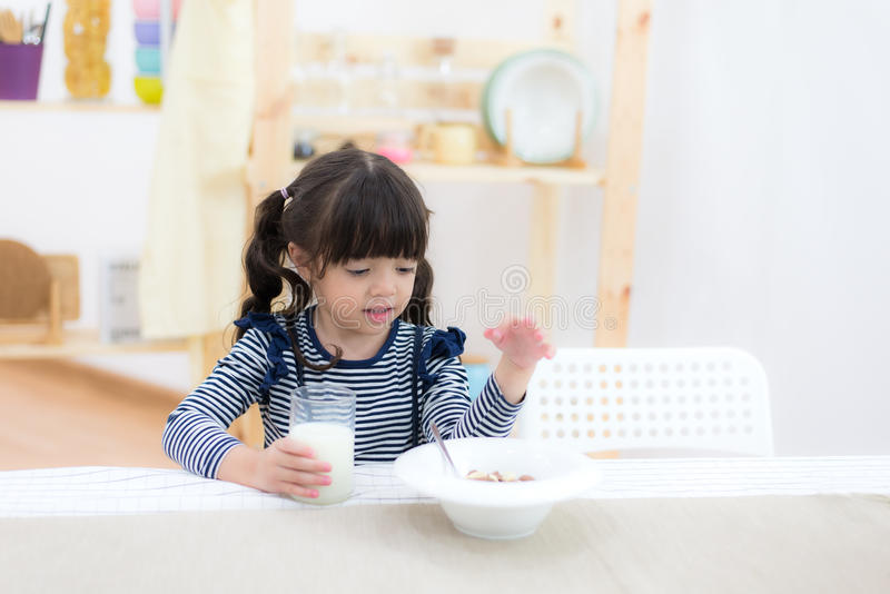 Cute little girl with milk mustache holding glass of milk royalty free stock photography