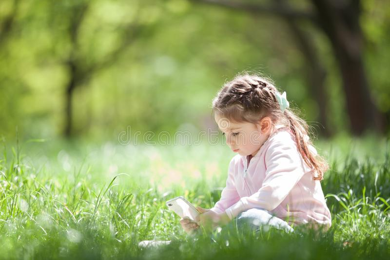 Cute little girl with mobile phone in the park. Family outdoor lifestyle. Happy small sitting on green grass. Beauty nature at royalty free stock photos