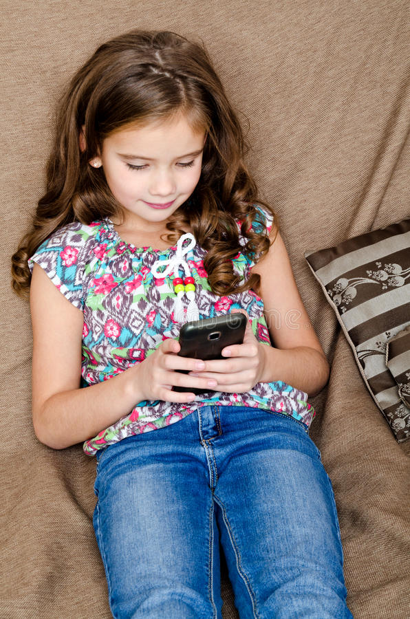 Cute little girl with mobile phone sitting on the sofa stock image