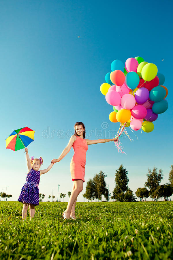 Cute little girl with mother colored balloons and rainbow umbrella holding in the park. Smiling child and mom on a field with fl royalty free stock image