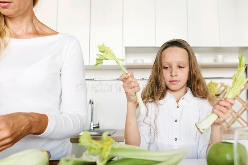Cute little girl mother cooking healthy food celery apple kitchen home morning Healthy lifestyle concept royalty free stock photos