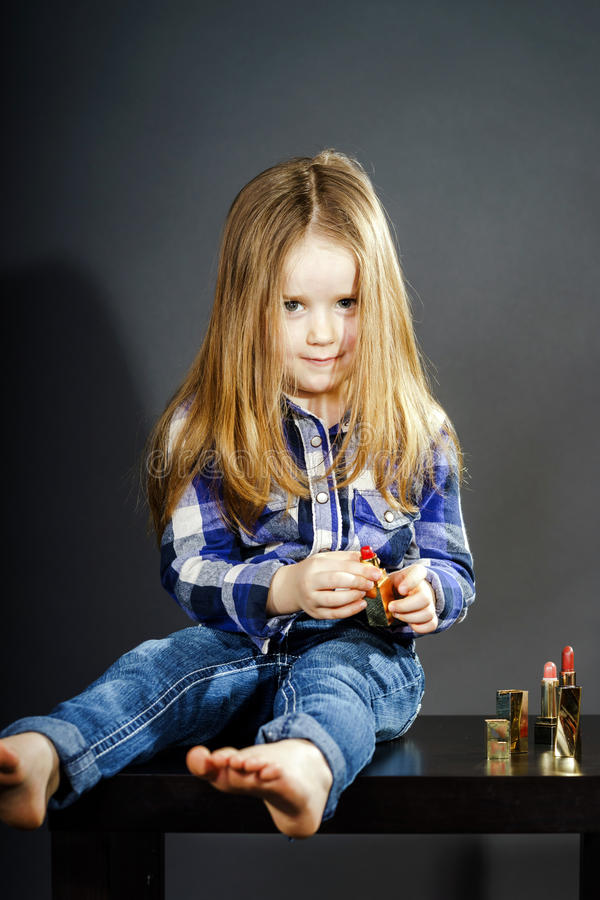 Cute little girl with mother's cosmetics, close-up portrait stock photos