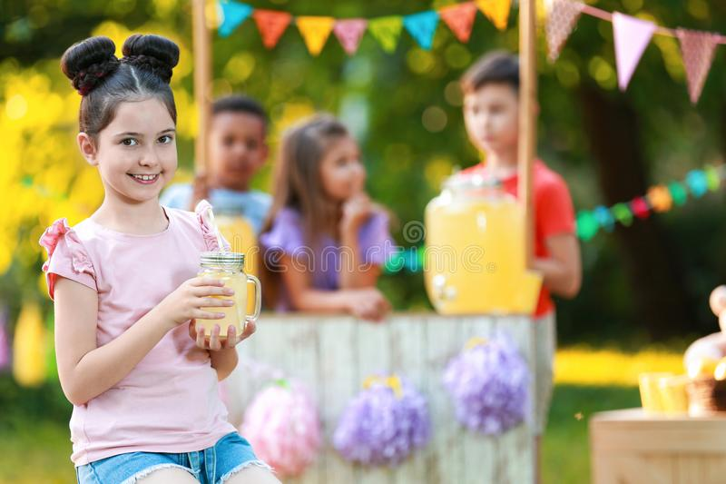 Cute little girl with natural lemonade in park. Summer refreshing drink stock photography