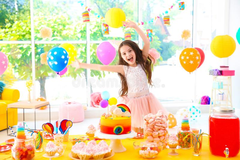 Cute little girl near table with treats at birthday party royalty free stock photos