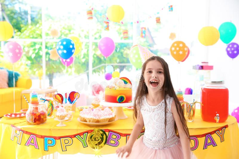 Cute little girl near table with treats at birthday party royalty free stock photography