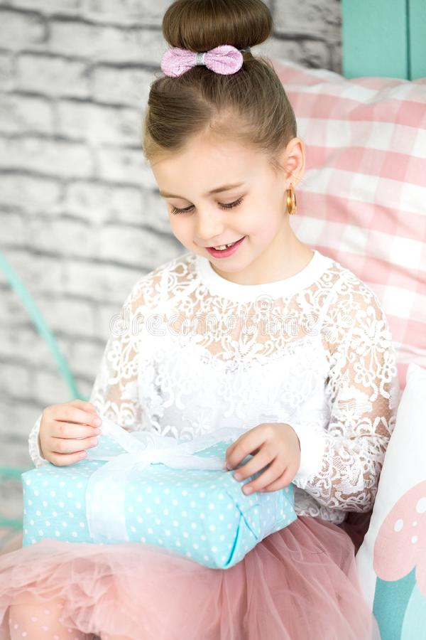 Cute little girl opens a birthday present stock photography