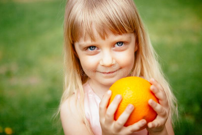 Cute little girl with orange fruit outdoors in summer stock photography