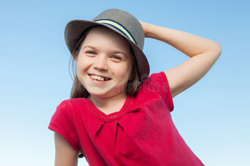 Cute little girl outside wearing a red shirt and a hat