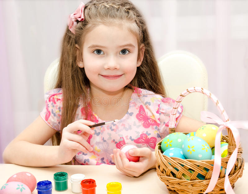 Cute little girl painting colorful easter eggs stock photography