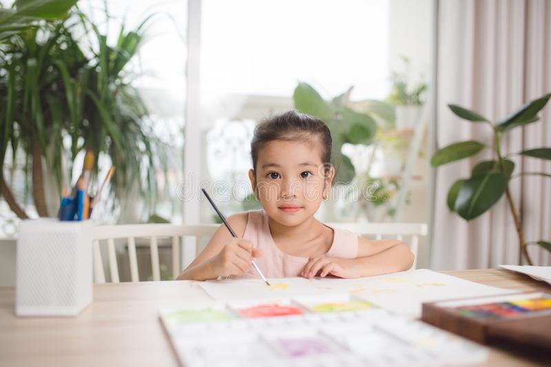 Cute little girl painting picture on home interior background.  royalty free stock photo