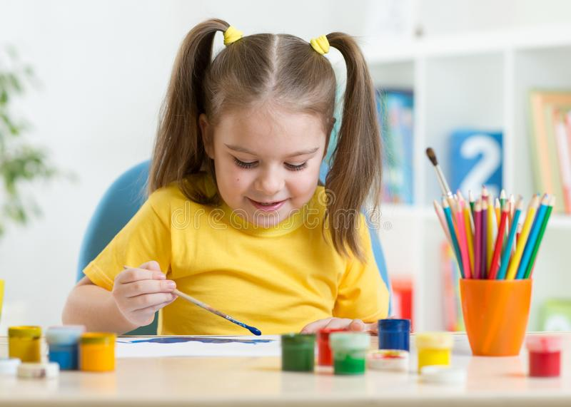 Cute little girl painting picture on home interior background royalty free stock photos
