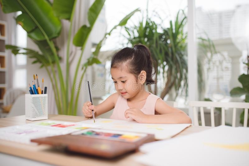 Cute little girl painting picture on home interior background.  royalty free stock photography