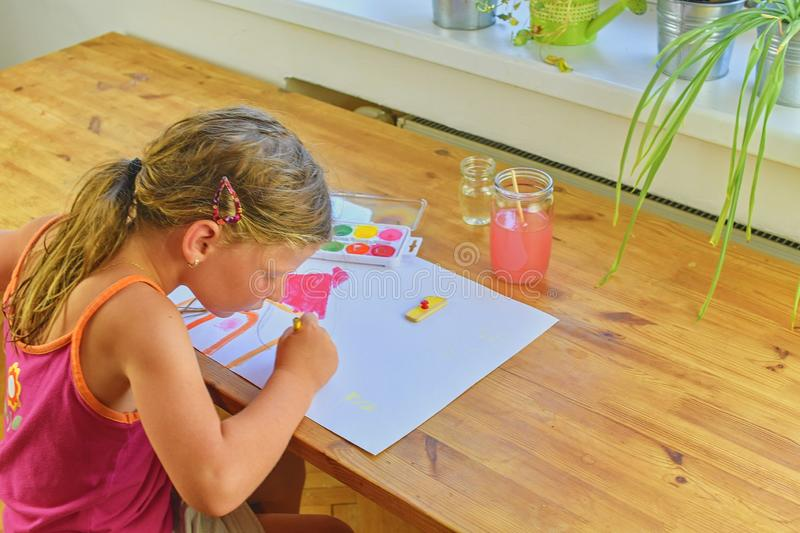 Cute little girl painting picture of house. Mortage concept. Selective focus, small DOF stock photos