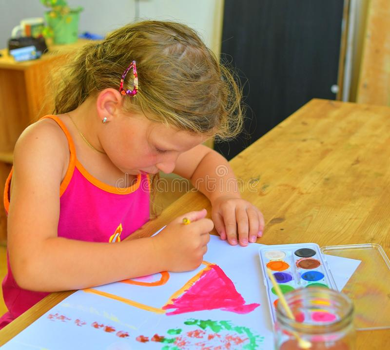 Cute little girl painting picture of house. Cute girl painting with watercolors. Mortage concept. Selective focus, small DOF royalty free stock photo