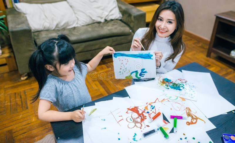 Cute little girl painting a picture with mother and show her work at home. stock image