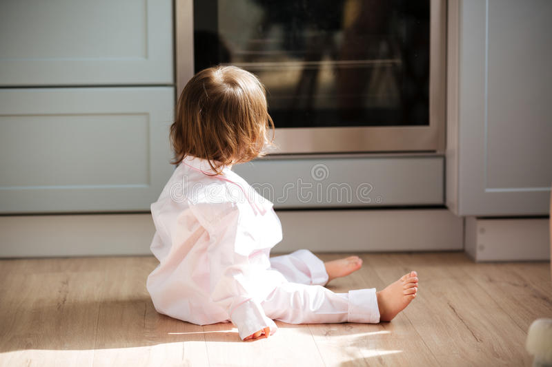 Cute little girl in pajamas sitting on wooden floor royalty free stock photo