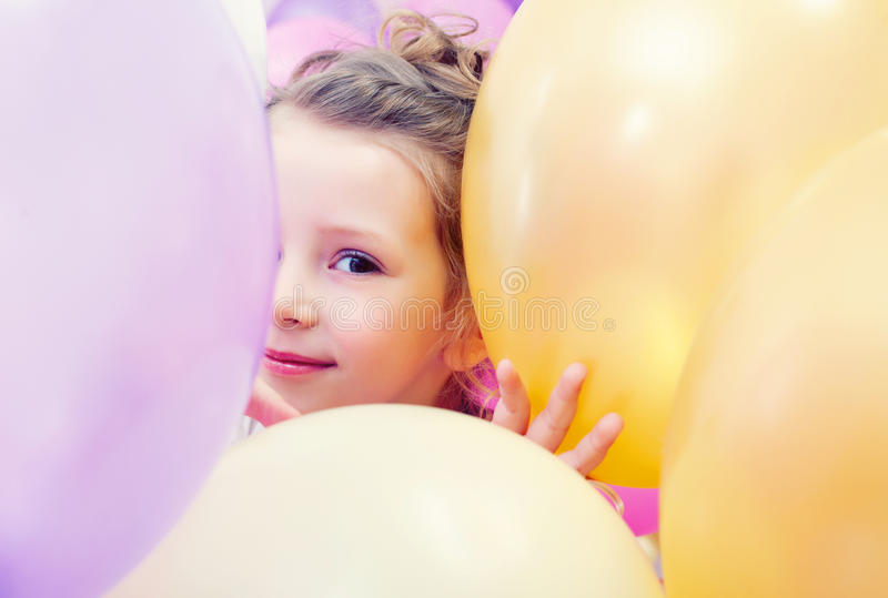 Cute little girl peeking out from behind balloons stock photo