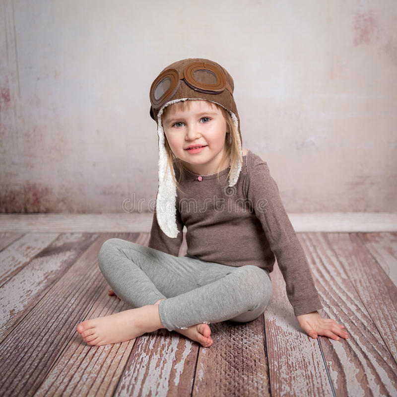 Cute little girl-pilot in hat. Cute little girl-pilot sitting on the floor in pilot hat royalty free stock photos