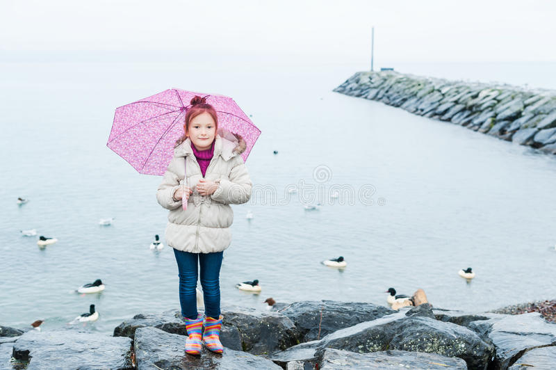 Cute little girl with pink umbrella. Standing by the lake on a cold weather stock photography