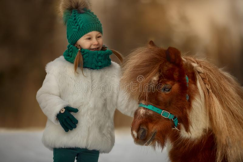 Cute Little girl with pinto pony stock images