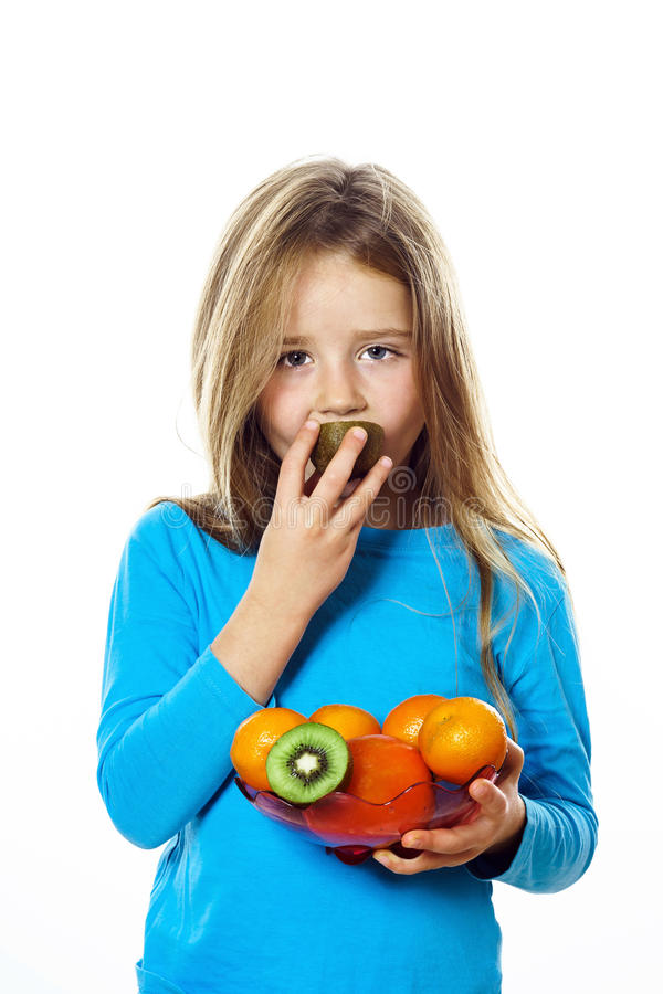 Cute little girl with plate of fruits: kiwi, date plum, mandarin stock images