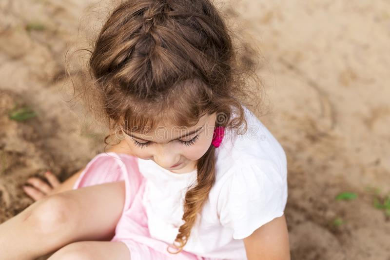 Cute Little girl play with sand in park on a summer day. stock photography