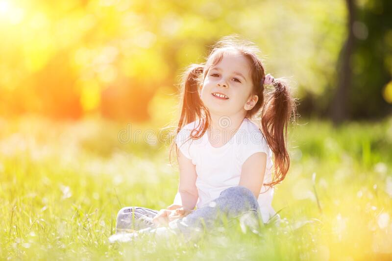 Cute little girl play in the sunny park. Beauty nature scene with colorful background at summer or spring season. Family outdoor stock photo