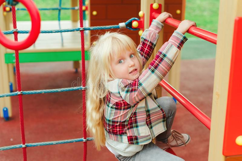 Cute little girl at playground outdoors. Adorable girl with long blonde hair. Happy child climbing on ladder at modern colorful stock photography
