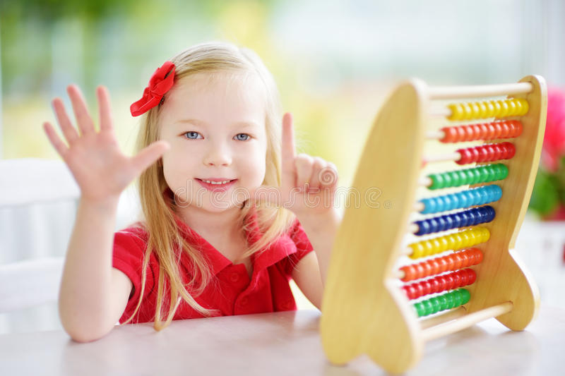 Cute little girl playing with abacus at home. Smart child learning to count. royalty free stock photography