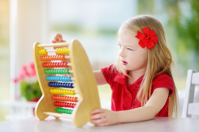 Cute little girl playing with abacus at home. Smart child learning to count. Preschooler having fun with educational toy at home or kindergarten stock photo