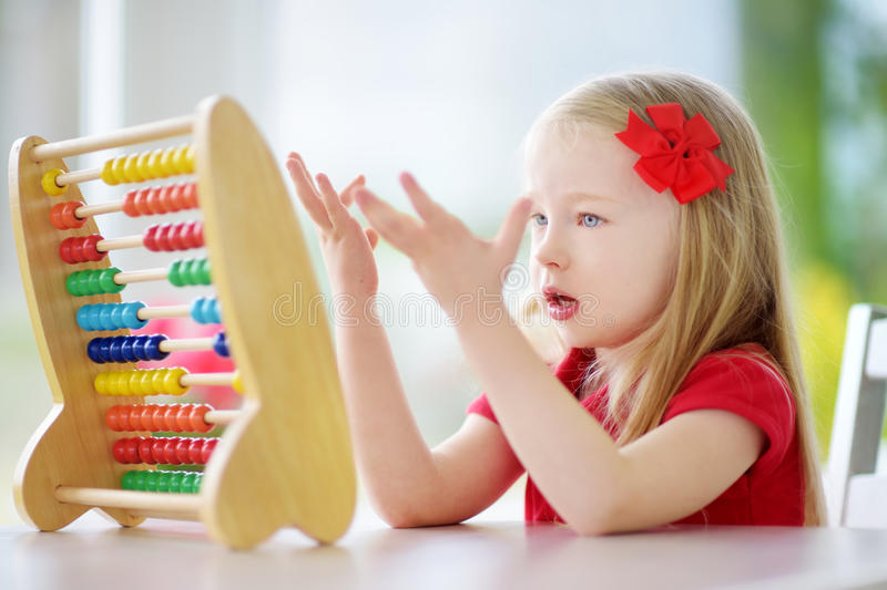Cute little girl playing with abacus at home. Smart child learning to count. royalty free stock photo