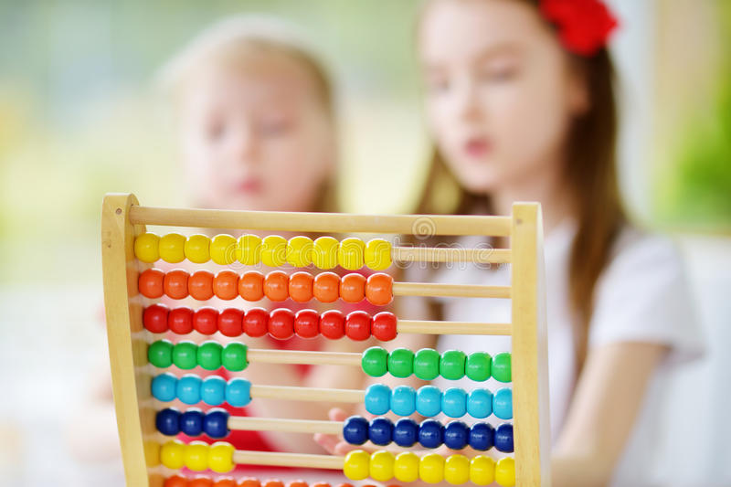 Cute little girl playing with abacus at home. Smart child learning to count. Two cute little girls playing with abacus at home. Big sister teaching her sibling royalty free stock photos