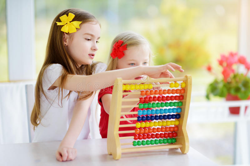 Cute little girl playing with abacus at home. Smart child learning to count. Two cute little girls playing with abacus at home. Big sister teaching her sibling stock photo