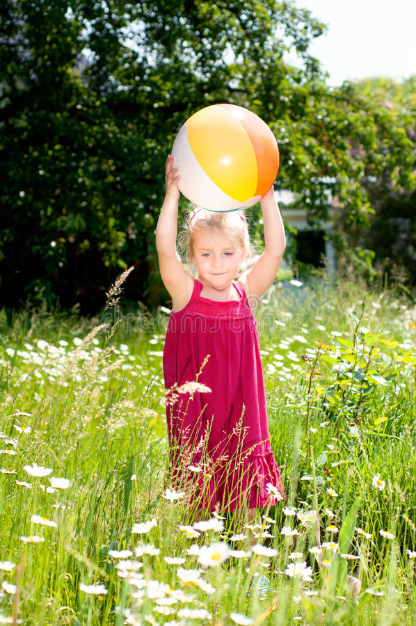 Cute little girl playing with a ball on a meadow stock photos