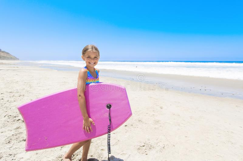 Cute little girl playing on the beach ready to boogie board in the ocean on vacation stock photos