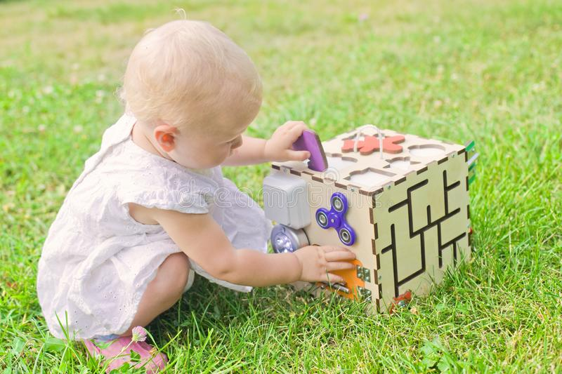 Cute little girl is playing with busiboard outdoors on green grass. Educational toy for toddlers. girl opened door to cube of stock photo