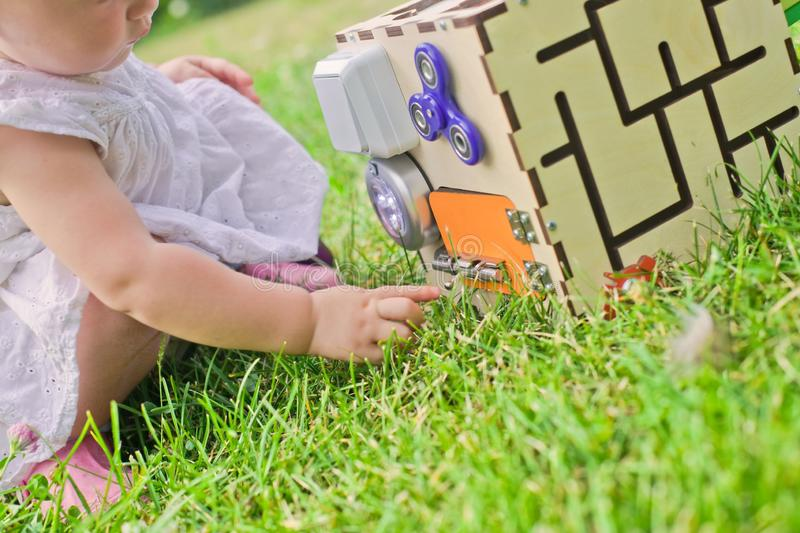 Cute little girl is playing with busiboard outdoors on green grass. Educational toy for toddlers. girl opened door to cube of royalty free stock image
