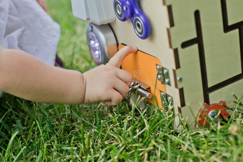 Cute little girl is playing with busiboard outdoors on green grass. Educational toy for toddlers. girl opened door to cube of royalty free stock photography