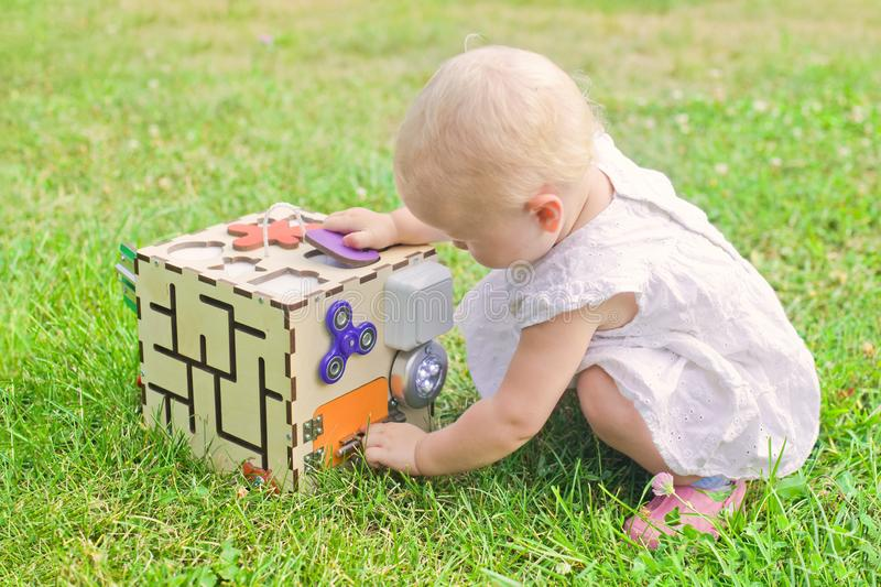 Cute little girl is playing with busiboard outdoors on green grass. Educational toy for toddlers. girl opened door to cube of stock images