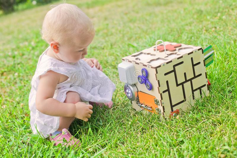 Cute little girl is playing with busiboard outdoors on green grass. Educational toy for toddlers. girl opened door to cube of stock photography